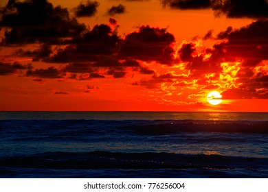 Sunrise on the horizon with bright red sky and sea with swell