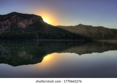 Sunrise on a lake with the sun rising behind the mountains
