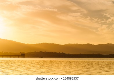 Sunrise on morning landscape, At the edge of the reservoir on mountain background