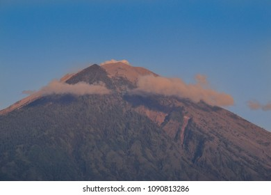 Sunrise on Mount Agung, Bali Indonesia. The peak is surrounding by cloud with a blue sky background.