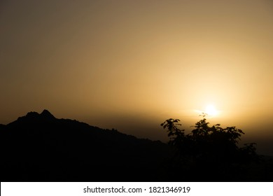 Sunrise on the mountain, with the silhouette of the peaks, contrast of light and shadow.