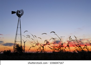Sunrise on an old farm water pumping windmill in Central Illinois.  Most of these have already disappeared from our landscape. Love the juxtaposition of the new wind turbines in the background.