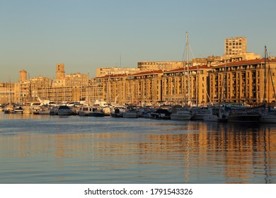 Sunrise on the old harbor of Marseille, France, with recreational boats and historical buildings