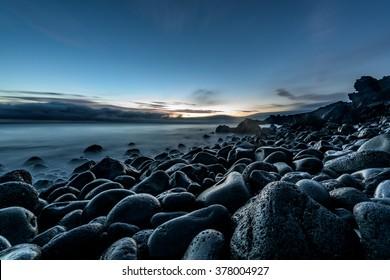 Sunrise on a pebble beach on the coast of Pico island