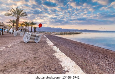 Sunrise on a public beach in Eilat - famous tourist resort and suitable for perfect vacations and holidays, entertainments and shopping, relaxing at sandy beaches, swimming and unforgettable diving