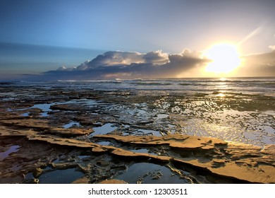 Sunrise on rocky beach - against sun. Shot in Sodwana Bay Nature Reserve, KwaZulu-Natal province, Southern Mozambique area, South Africa.