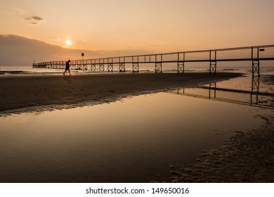 Sunrise on sea with person walking and a bridge