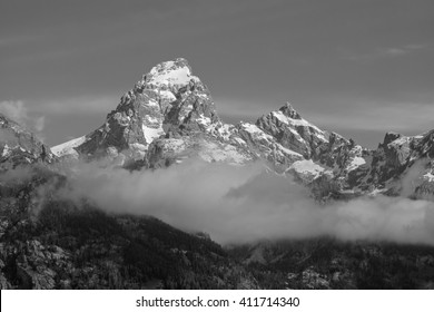 Sunrise on the snow capped Grand Teton with fog in the foreground.