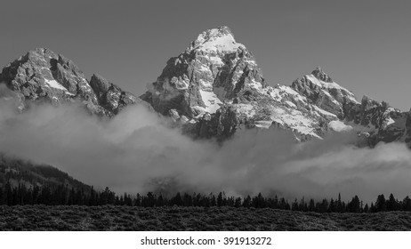Sunrise on the snow capped Teton Range with fog in the foreground.