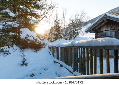 sunrise on snow covered fence and hut in winter