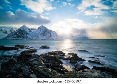 Sunrise on the stone shore of the ocean and mountains with snow on the horizon