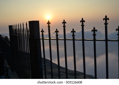 Sunrise on top of iron fences in clouds