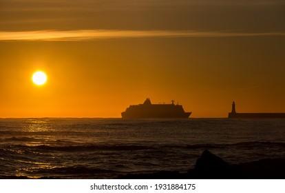 Sunrise on Tynemouth's Longsands beach as a passenger ferry heads towards the Tyne to dock