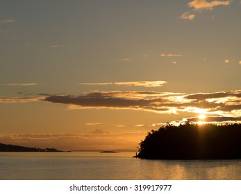 Sunrise on west coast of British Columbia, showing sun rising through clouds over an island.  Still ocean waters in foreground