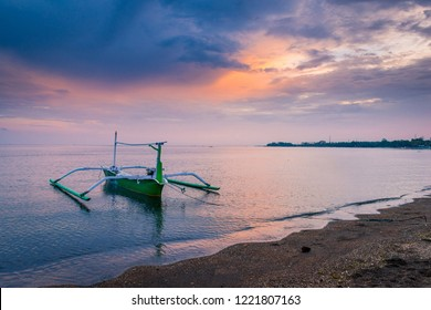 Sunrise on the white sandy beach with a boat floating on the ocean