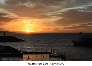 Sunrise at one end of the marina in Ponta Delgada, Azores. In the background  there is a silhouette of a ferry coming into port and a silhouette  of a lighthouse.