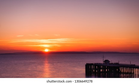 Sunrise in orange, coral, red, and yellow over the sea, Penarth pier and a sky in magenta colors.