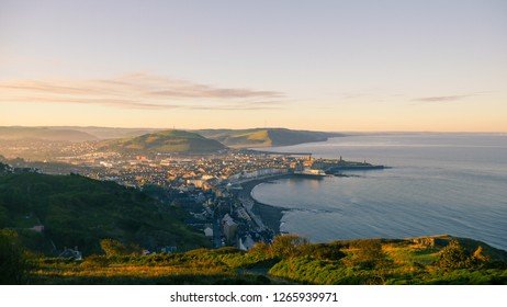 Sunrise over aberystwyth mountains next to the sea