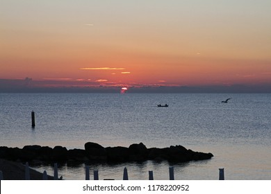 Sunrise over the Adriatic Sea in late summer on the Italian Riviera near Porto Recanati and Numana in Ancona with fishing boats in the distance and closed beach umbrellas waiting for holiday makers