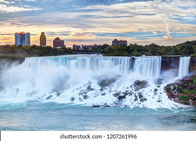 Sunrise over American Falls and Bridal Veil Falls at Niagara Falls, New York State, USA, with cityscape in the background.