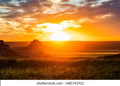Sunrise over a butte in grass plains of Colorado