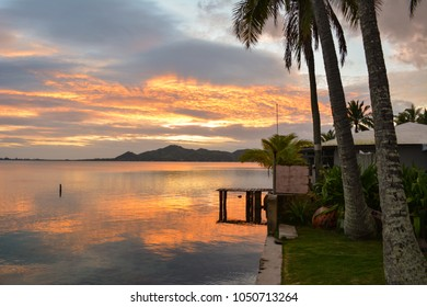 Sunrise over a calm Kaneohe Bay on Oahu, Hawaii.  The sun creates a stunning reflection over the flat water surface.