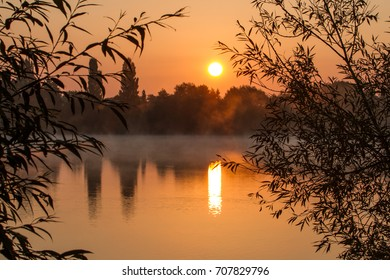 Sunrise over a calm lake on a misty autumnal morning, UK