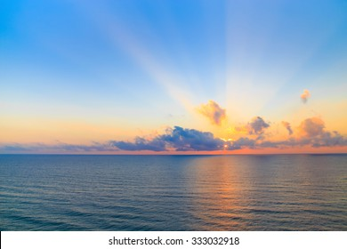 Sunrise over a calm ocean casting beams of orange light into the air as the setting sun penetrates the clouds above in a scenic tranquil seascape.