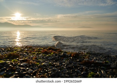 The sunrise over the calm sea casts rays of orange light into the air as the setting sun penetrates through the clouds into the picturesque calm seascape, the sea. - Shutterstock ID 1992632669