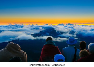 Sunrise over clouds and distant mountains from on top of Haleakala Crater, Maui, Hawaii, USA