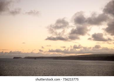Sunrise over the Cornish coastline looking towards the headland and island at Tintagel.