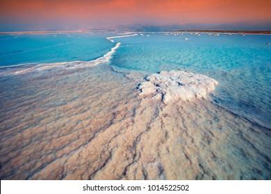 Sunrise over Dead Sea. Salty textured sea shore.