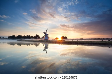 sunrise over Dutch windmill and river, Holland