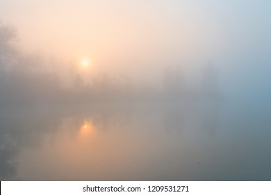 Sunrise over foggy lake. Sun disk rising up through the trees on the river bank.