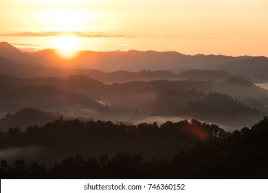 Sunrise over the forest mountain and the mist.