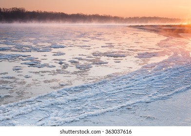 Sunrise over a freezing river covered in fog