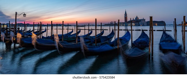 Sunrise over the Grand Canal in Venice with gondolas bobbing in the foreground and venetian buildings and blue/orange sky in the background.