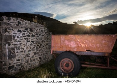 Sunrise over the hill with old farm trailer and stone wall in foreground.