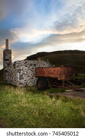 Sunrise over the hill with old farm trailer and ruined stone house with chimney.