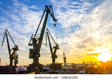 Sunrise over historical port cranes in the industrial part of the city Gdansk (Gdańsk) in Poland (Polska). Popular tourist destination - shipyard known all over the world.