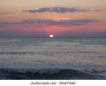 Sunrise over the Indian ocean at Kanyakumari with orange, red sky, dark purple clouds and waves in the ocean