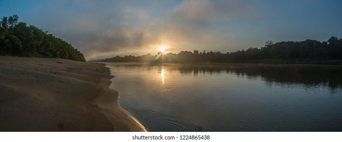 Sunrise over the Javarii  river, tributary of the Amazon. Sandy beach in Amazon jungle, during the low water season. Amazonia. Selva on the border of Brazil and Peru. South America. Dos Fronteras.