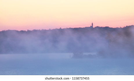 Sunrise over lake Ammersee on a misty morning