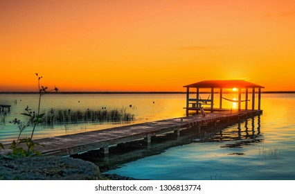 Sunrise over lake bacalar mexico, with dog sitting on the dock