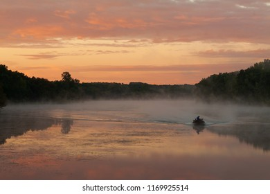 Sunrise over lake with fishing boat moving toward camera out of the mist rising from the water.  Yellow and purple hue sky and reflection in the lake