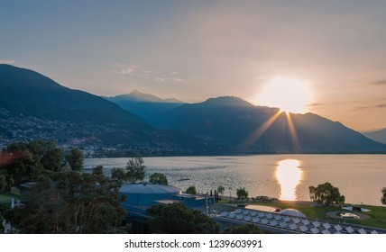 Sunrise over the lake of Locarno looking at Minusio e Tenero, early morning with clear skySunrise over the lake of Locarno looking at Minusio e Tenero, early morning with clear sky