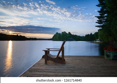 Sunrise over a lake in Muskoka, Canada. Chair sitting on a wooden dock. In background other chairs are visible along with a sailboat and a cottage nestled between green trees. Long exposure shot.