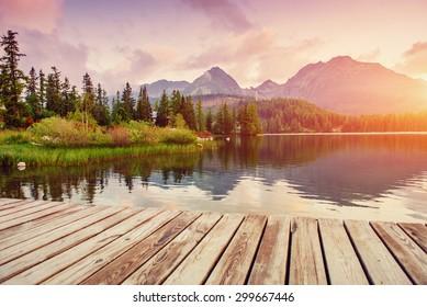 The sunrise over a lake in the park High Tatras. Shtrbske Pleso, Slovakia, Europe.