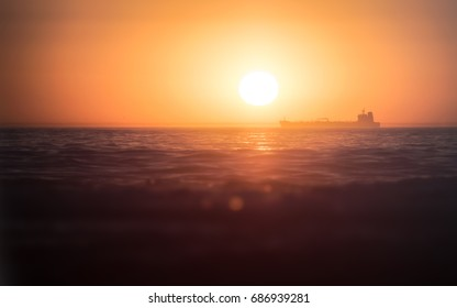 Sunrise over a large ship out in the ocean