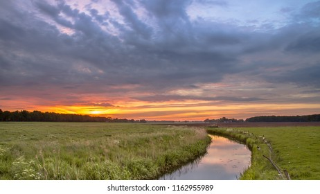 Sunrise over lowland river valley landscape near Oosterwolde, Netherlands
